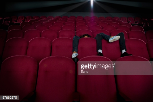 87882875-couple-in-empty-cinema-legs-over-seats-faces-gettyimages